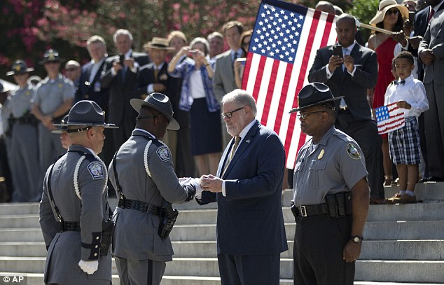 An honor guard member from the South Carolina Highway Patrol hands the Confederate battle flag that flew in front of the Statehouse to the curator of the Confederate Relic Room and Military Museum