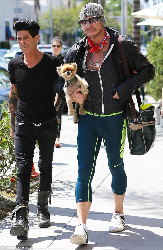 Taking the Mickey for a walk: Rourke was accompanied by a handsome companion and his pooch as he went for a meal in Beverly Hills on Thursday