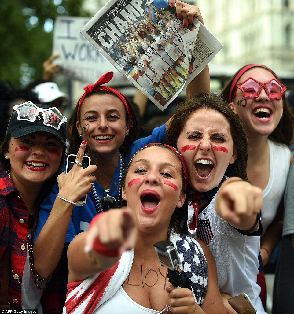 USA women's soccer team fans with painted faces cheered before the parade while clutching their phones and an old newspaper