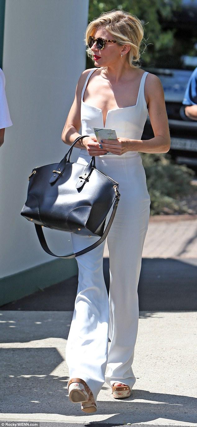 British actress Sienna Miller, 33, stunned in a classy white jumpsuit which was teamed with wedged platforms