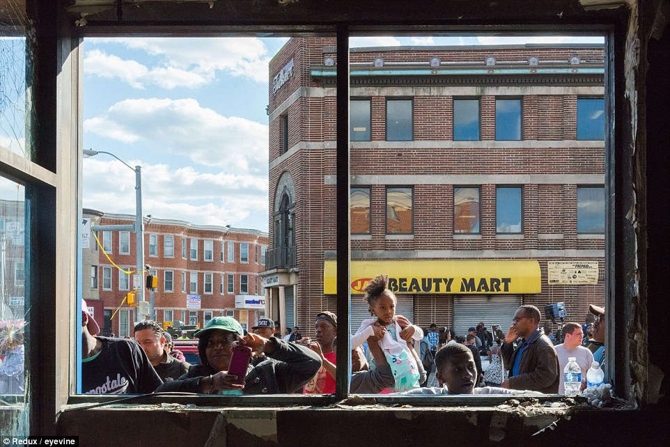 Onlookers peer into the CVS that was destroyed during the protests that hit northwest Baltimore after the funeral of Freddie Gray on Monday