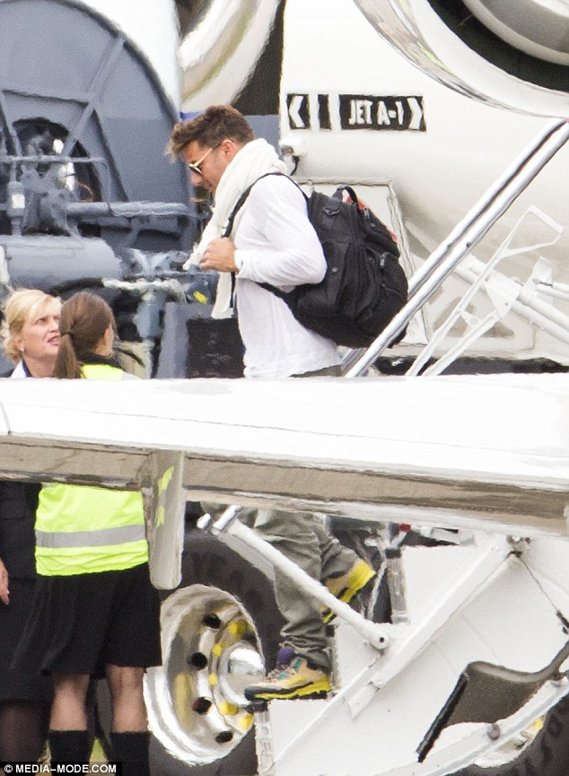 Multi-tasking daddy: The singer appeared in high spirits as he helped his little ones Matteo and Valentino off the plane while lugging his black rucksack on his perfectly toned shoulders