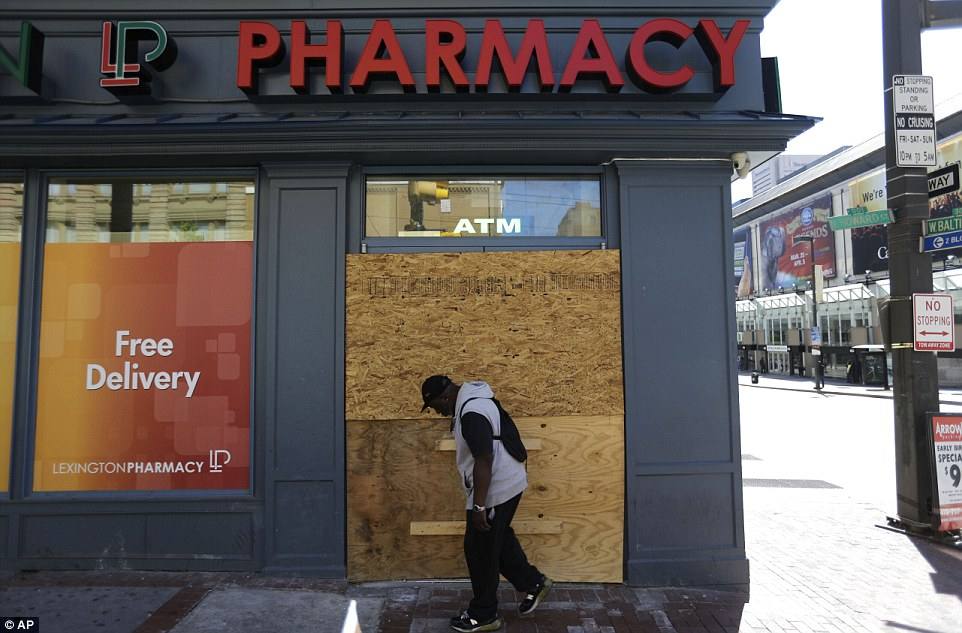 Protection: A store entrance is boarded up as a pedestrian walks through downtown on Wednesday after tensions seemed to ease after Monday's fiery riots
