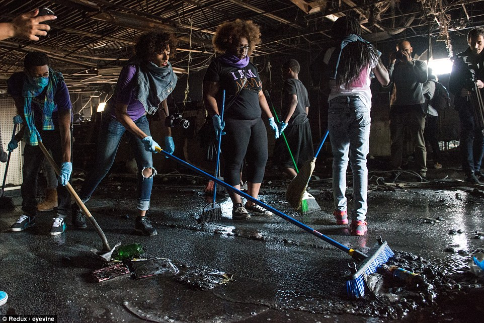 Community spirit: Volunteers help clean the CVS that was destroyed during protests over the death of Freddie Gray