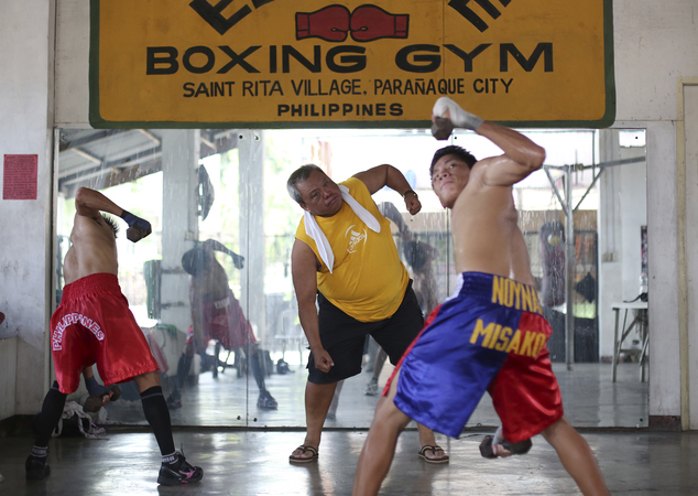 In this April 22, 2015, photo, Filipino boxing promoter and trainer Gabriel Elorde Jr., center, trains boxers at his boxing gym in suburban Paranaque, south ...