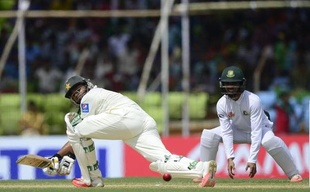 Pakistan batsman Azhar Ali (left) plays a shot as Bangladesh fielder Mominul Haque looks on during the first Test match between Bangladesh and Pakistan at th...