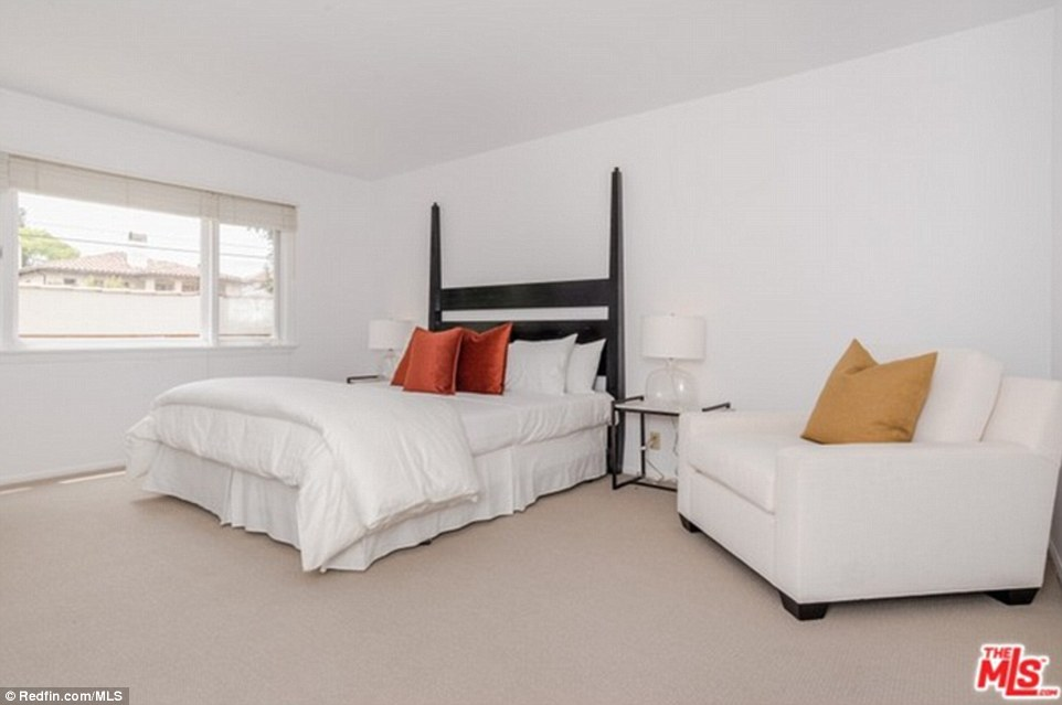 A second bedroom is also simple in its decor with just a bed featuring a black headboard, a small chaise-like chair, and two side tables