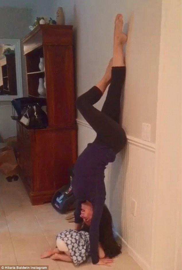 'Uno, dos, tres...': Hilaria Baldwin shared a video of herself Thursday performing 10 upside-down tricep dips as her daughter Carmen crawled beneath her