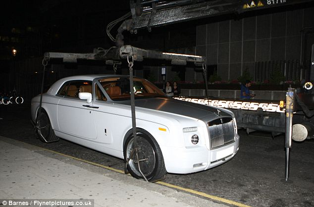 Taxing situation: The white luxury Rolls Royce was spotted without a tax disc today so officials decide to tow it away