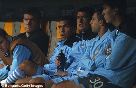 Act of defiance: Tevez (fourth right) watches from the bench