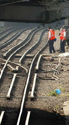Repairs: Engineers are shown checking cables running to signals. Thieves in Leeds managed to delay 160 trains by just stealing a small amount of cable