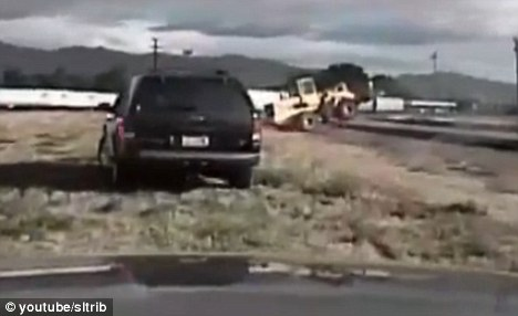 Foiled again: The front-end loader evades police as it goes over train tracks on Monday