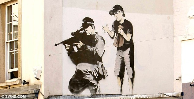 Before the attack: The artwork  depicted a crouched police marksman with a child about to burst a paper bag behind him before it was vandalised