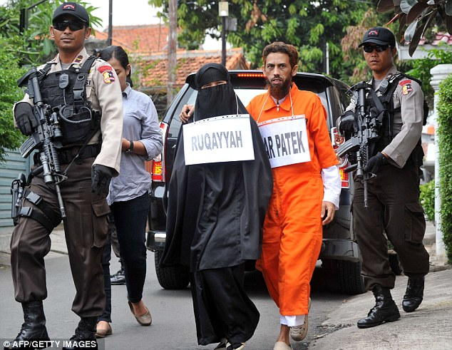 Armed guard: Patek and his wife are followed closely by police officers carrying weapons during the reconstruction in Jakarta, Indonesia