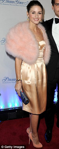Odd ensemble: Olivia paired the look with a mismatched pink fur shawl, her hair pulled back into a tight bun