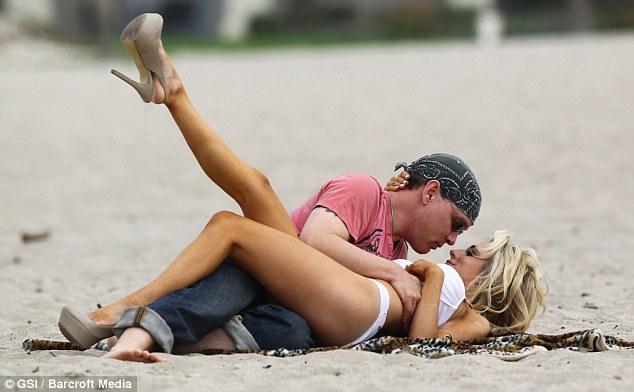 I get a kick out of you: Courtney flings her leg in the air as she snuggles up to her husband