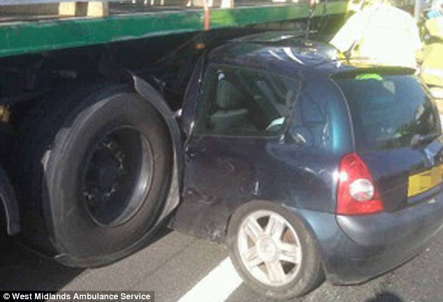 Lucky escape: The woman driver was unhurt after her car was dragged underneath a lorry along the motorway for hundreds of yards