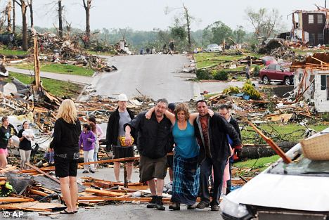 Devastation: Residents of Joplin help a woman who survived the tornado in her basement