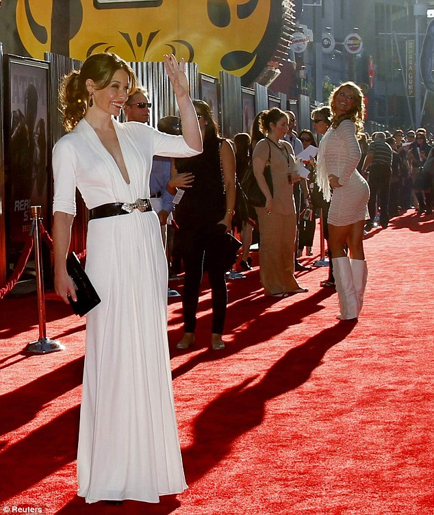 Graceful: Evangeline Lilly looked stunning in a flowing white gown which was split almost down to the navel as she arrived to the Los Angeles premiere of Real Steel tonight