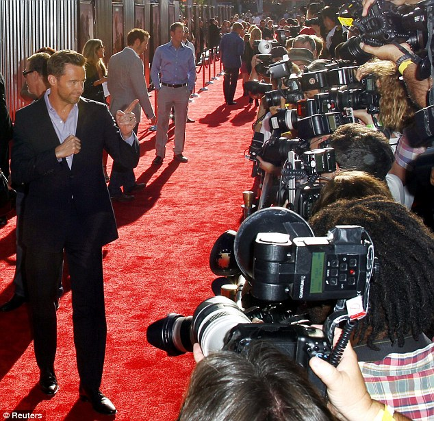 Leading man: Jackman looked dapper in a dark suit and shirt as he posed in front of the teams of photographers at the event