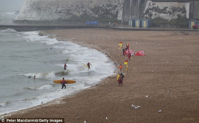 Soggy: Lifeguards train on an empty beach at Viking Bay, Broadstairs, Kent, today after the bad weather moves in