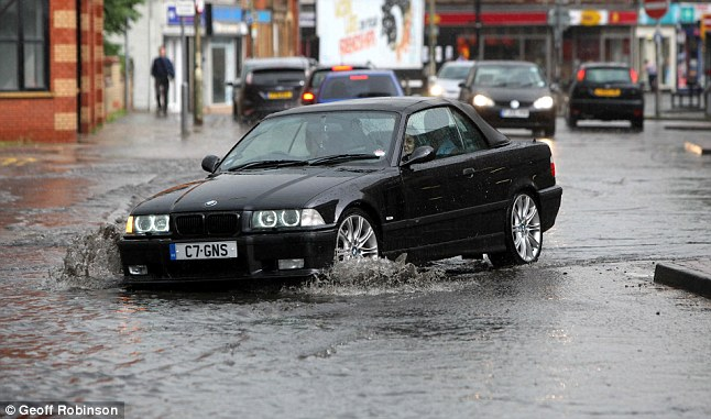 Puddle trouble: A motorist in Peterborough makes their way through the city centre yesterday