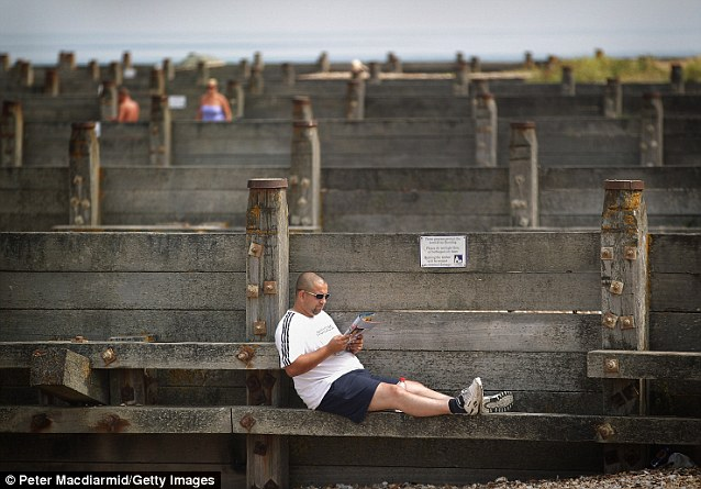 Lapping it up: A man in Whitstable makes use of the sun to read on his own on Wednesday