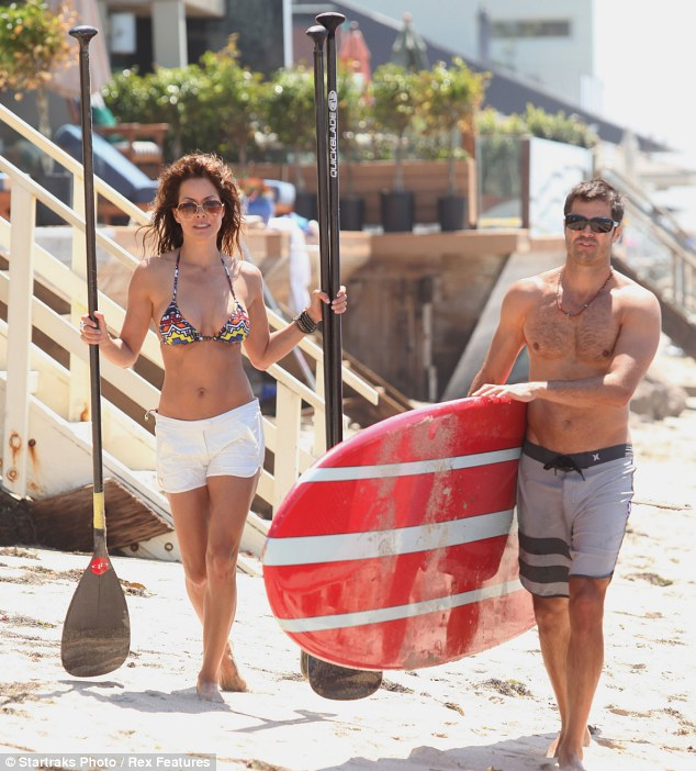 Getting physical: The Dancing with the Stars co-host and her former Baywatch star fiance like to stay active by paddle boarding