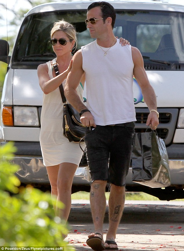 The loving touch: Jennifer Aniston places her hands on Justin Theroux as the couple enjoy a shopping trip in Kauai, Hawaii
