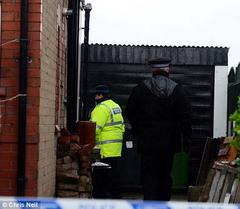 Search: Officers enter the house near a black garage following the grim discovery on Saturday