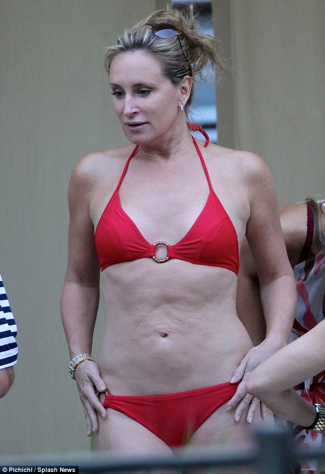 Revved up in red: The 48-year-old finally put a smile on her face when she opted for the red, with her curvaceous figure and a slight ripple in her tummy on display