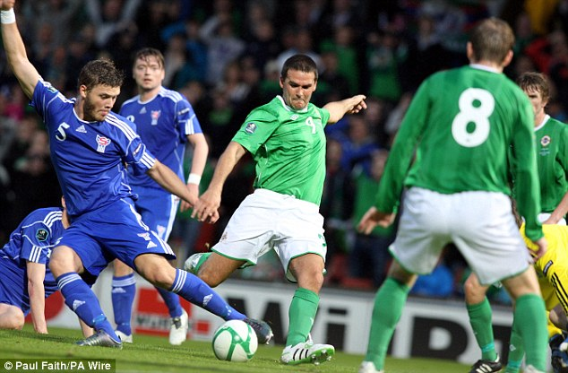 Close call: David Healy beats the goalkeeper but hits the post