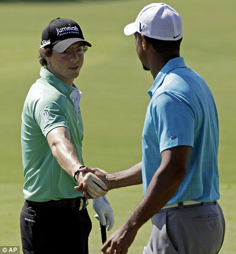 Passing the baton: Rory McIlroy shakes hands with Tiger Woods