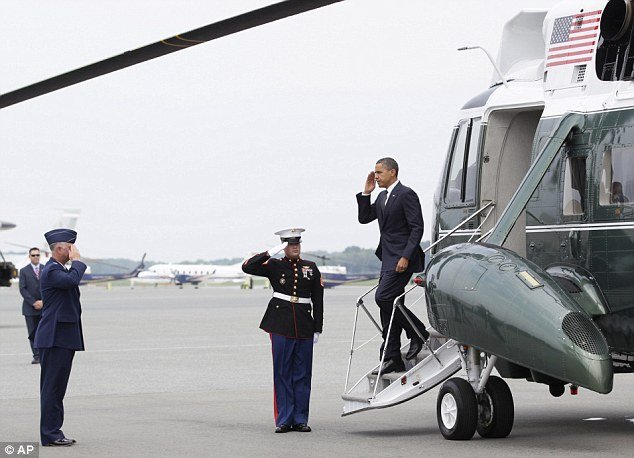 Arrival: President Barack Obama salutes as he is greeted by Col. Mark Camerer, the 436th Airlift Wing Commander, left, as he steps off of Marine One, at Dover Air Force Base, Delaware, on Tuesday
