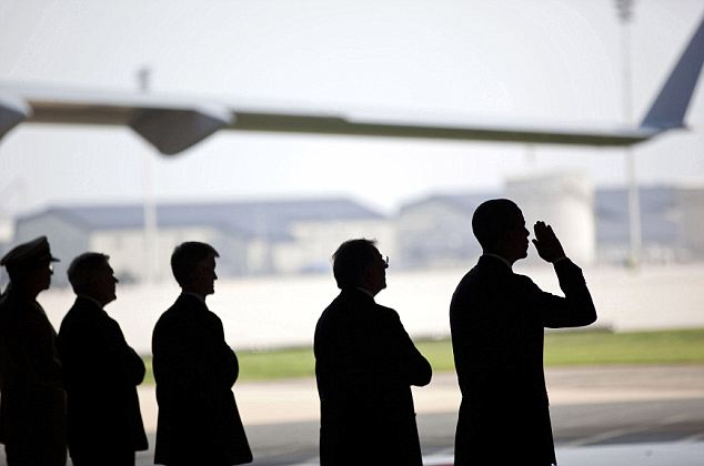 No press was allowed at Dover Air Base, but White House photographer Pete Souza capture Obama saluting on Tuesday at the ceremony for the 'dignified transfer' of the remains