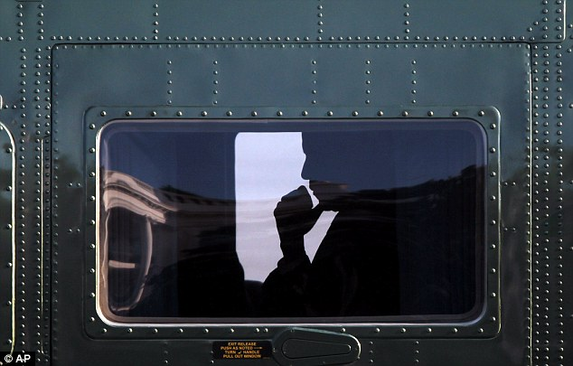 Pensive: President Obama is seen silhouetted inside Marine One helicopter during his arrival on the South Lawn of the White House after his unannounced trip to Delaware