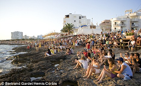 Revellers flock to the chill-out zone in San Antonio Bay, Ibiza - five Brits have died on the island so far this summer