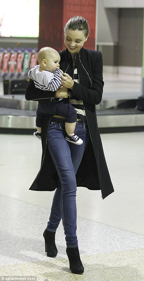 Model behaviour: Despite the unglamorous backdrop of Melbourne airport, Miranda Kerr still looked perfect as she walked with son Flynn