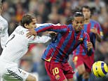 Madrid, SPAIN:  Real Madrid's Michel Salgado (L) vies with Barcelona's Ronaldinho (R) during their Spanish League football match at Santiago Bernabeu stadium in Madrid, 19 November, 2005.  AFP PHOTO JAVIER SORIANO  (Photo credit should read JAVIER SORIANO/AFP/Getty Images)