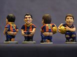 """A picture taken on November 19, 2015 shows ceramic figurines of (L-R) Barcelona's Uruguayan forward Luis Suarez, Barcelona's Argentinian forward Lionel Messi and Barcelona's Brazilian forward Neymar called """"Caganers"""" during their presentation in Torroella de Montgri, near Gerona. Statuettes of well-known people defecating are a strong Christmas tradition in Catalonia, dating back to the 18th century as Catalans hide caganers in Christmas Nativity scenes and invite friends to find them. The figures symbolize fertilization, hope and prosperity for the coming year. AFP PHOTO / LLUIS GENELLUIS GENE/AFP/Getty Images"""