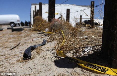 Danger country: A police cordon is seen at a crime scene where two men were gunned down by unknown assailants on the outskirts of Ciudad Juarez