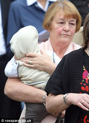 The couples orphaned son Jake is carried by his grandmother from the service