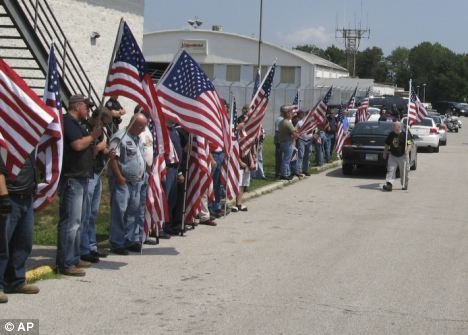 Human toll: Residents line the roadway at the Mid-Ohio Valley Regional Airport as a motorcade carries the body of Nicholas Null, killed on August 6