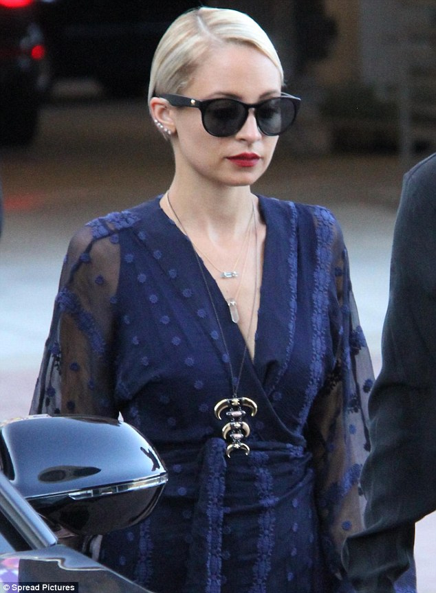 Casual glamour: The newly blonde beauty slicked back her locks in a side part and added a bold red lip to her eye catching look