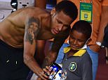 Brazilian player Neymar Junior makes a selfie with a boy after a training session in Salvador, Brazil on November 16, 2015, on the eve of a FIFA World Cup Russia 2018 qualifier match against Peru. AFP PHOTO / CHRISTOPHE SIMONCHRISTOPHE SIMON/AFP/Getty Images