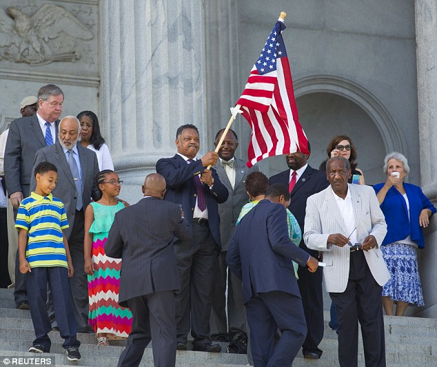Prominent civil rights figure Rev Jesse Jackson waves a Star Spangled Banner with joy at the ceremony