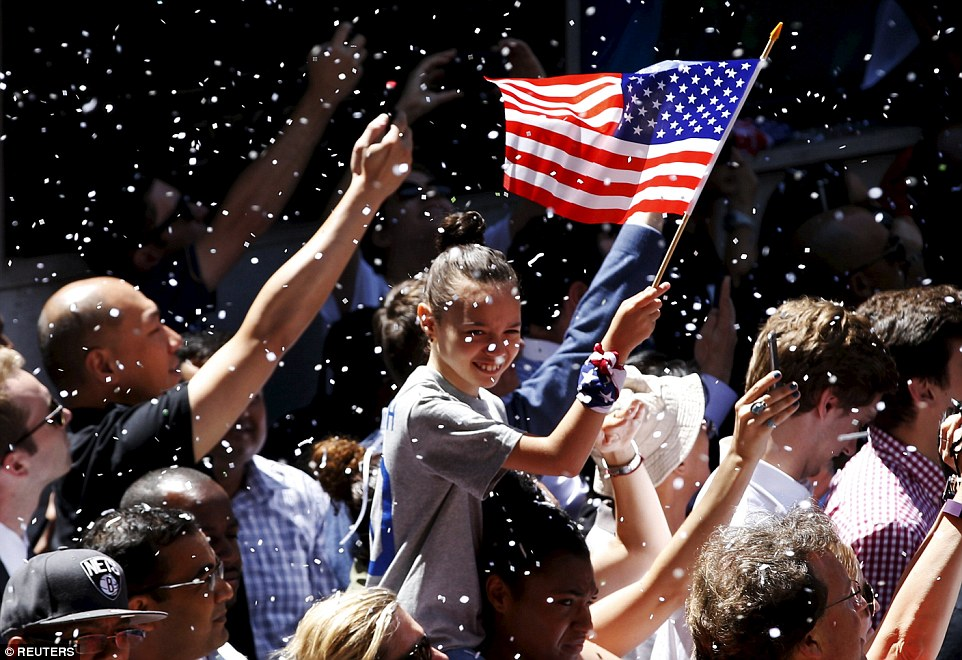 A fan holding an American flag couldn't hold back her smile as paper fell from the buildings above during the ticker-tape parade