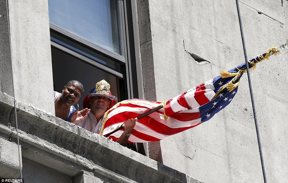 Fans leaned out of an office window and held an American flag outside as the parade through the Canyon of Heroes went past