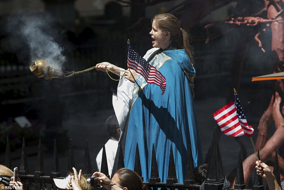 A clergy member spread incense as she stood outside Trinity Church near the intersection of Broadway and Wall Street on Friday