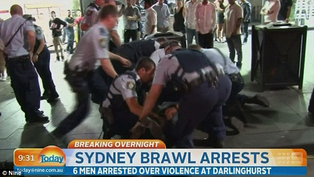 Police officers work together to subdue one of the six men arrested following the fight